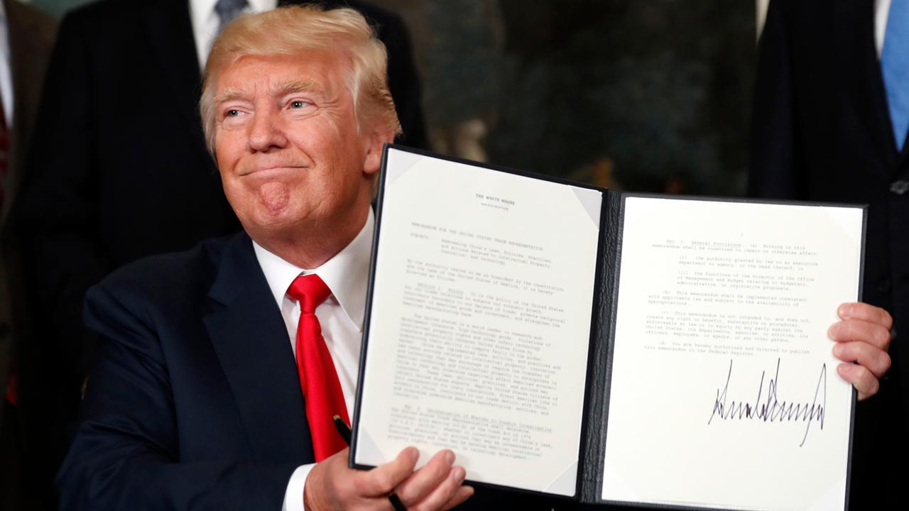 President Donald Trump signs executive action to order an investigation into Chinese trade practices.