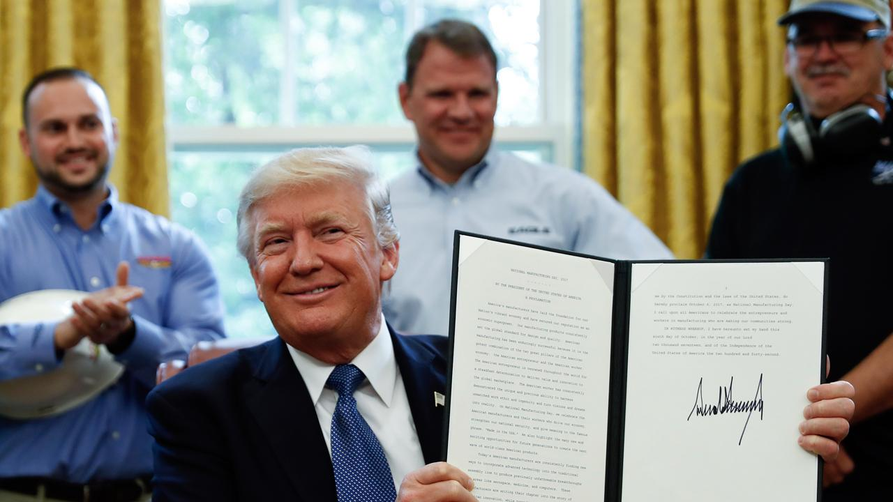 President Trump signs the National Manufacturing Day proclamation in the Oval Office.
