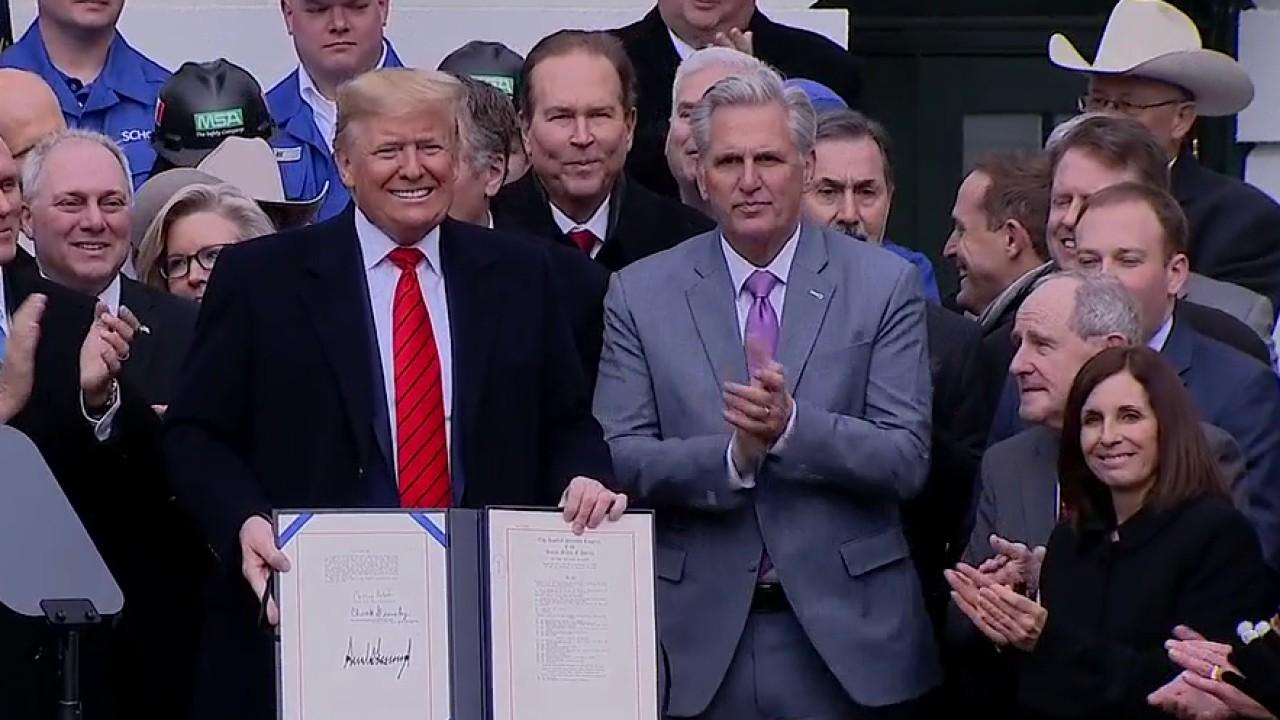 President Trump signs the USMCA into law with senators, administration officials and trade officials by his side.
