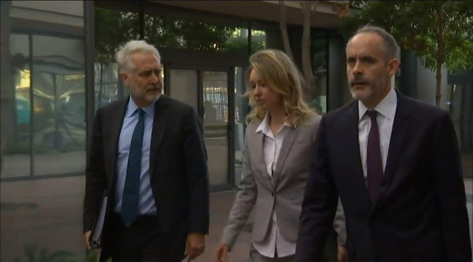 Former Theranos President Sunny Balwani enters a federal court building in San Jose, California accompanied by his legal team, followed by its former CEO Elizabeth Holmes.