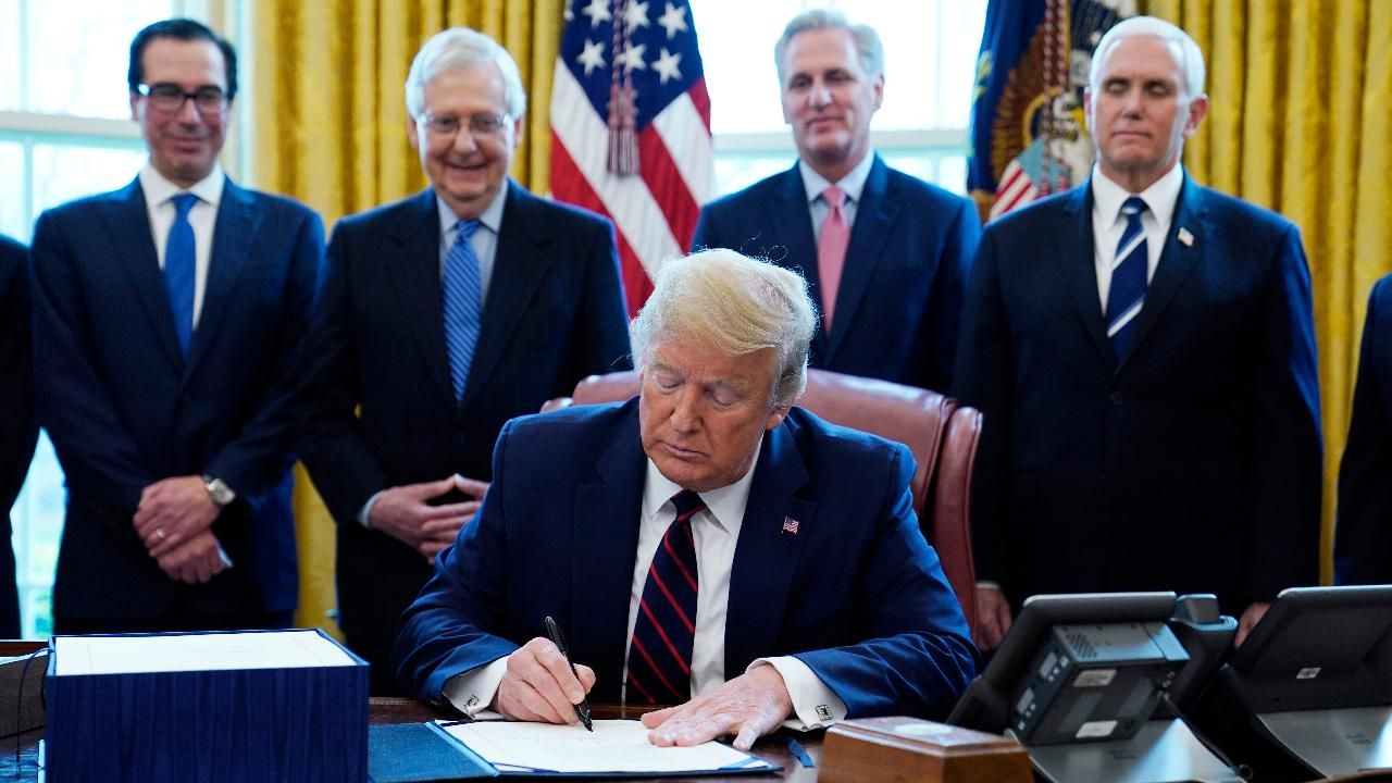 President Trump officially signs the $2 trillion coronavirus relief bill in the Oval Office.